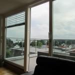 Kan se utsikt fra stue gjennom rekkverk i stål og glass